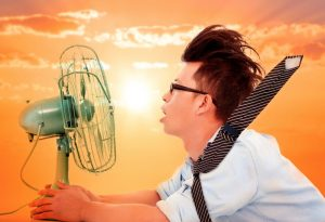 man-suffering-from-humidity-uses-electric-fan